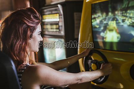 young woman using driving simulator in