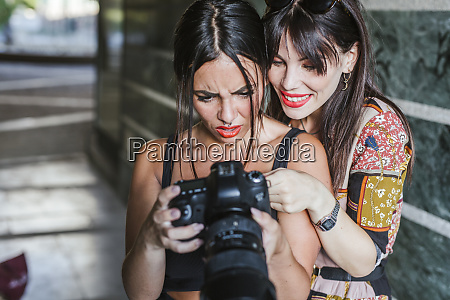 two young woman checking photos on