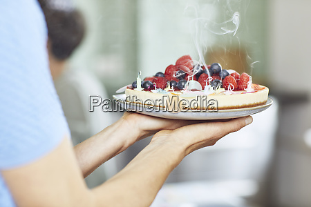 woman serving berry cake at birthday