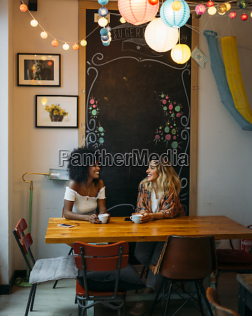 multicultural women talking in a cafe