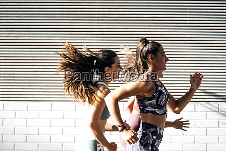 three sporty young women running in