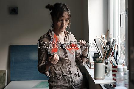 female artist holding broken glass pane