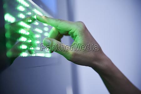 detail of finger touching green led