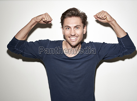 portrait of laughing man flexing muscles