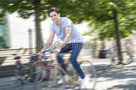 smiling man riding racing cycle