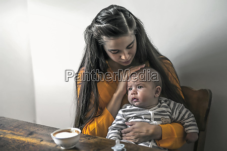 mother with baby sitting at wooden