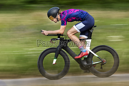 triathlete riding bicycle on country road