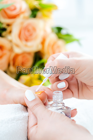 pedicurist applying white color to foot