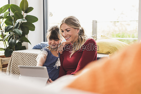 happy mother and daughter using tablet