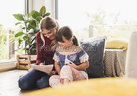 mother helping daughter with homework at