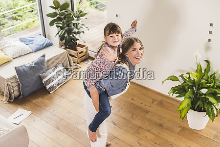 happy mother carrying daughter piggyback at