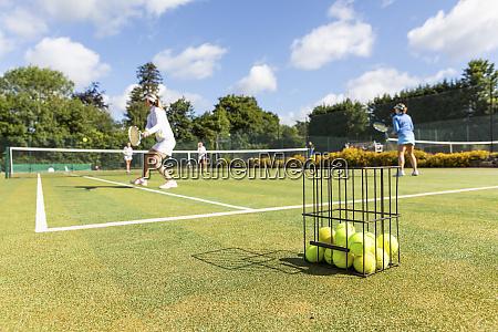mature women playing tennis on grass