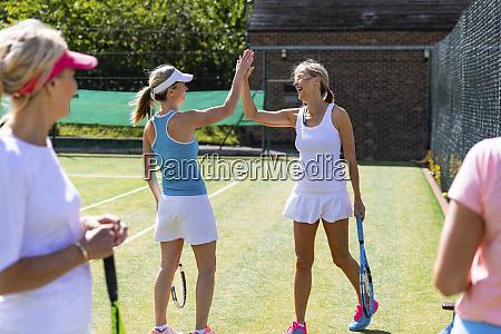 happy mature women celebrating after tennis
