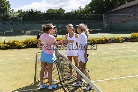 mature women finishing tennis match on