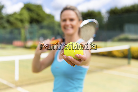 smiling mature woman holding a tennis
