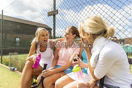 happy mature women talking at tennis