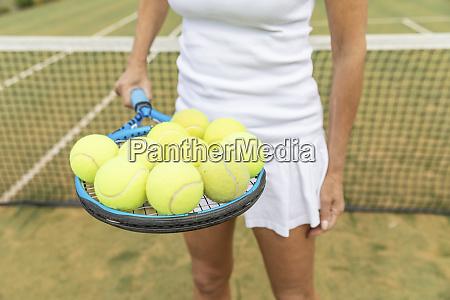 female tennis player holding a tennis