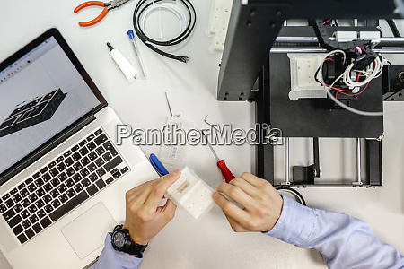 student setting up 3d printer overhead