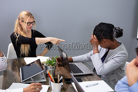 business woman blaming her colleague for