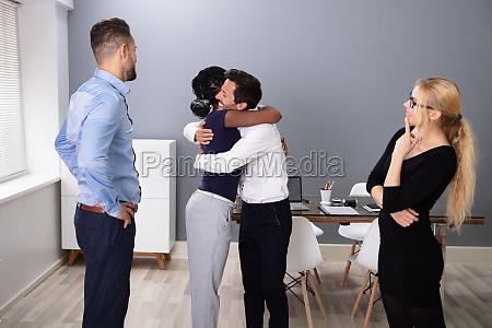 female employee hugging embracing happy coworker