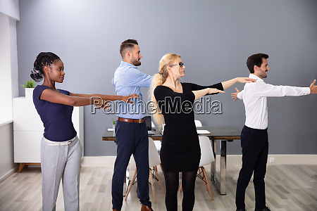 businesspeople doing exercise with hands outstretched