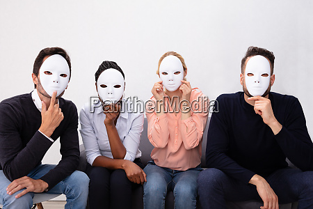 group of people wearing white masks