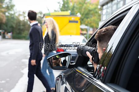 private detective taking photos of man