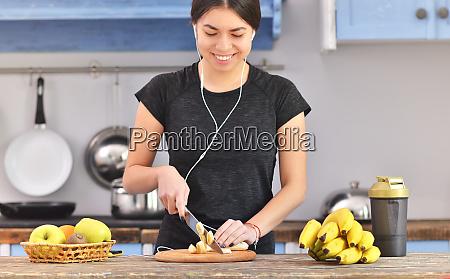 young woman preparing protein shake at