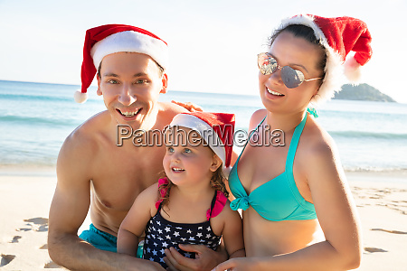 happy family wearing santas hat over