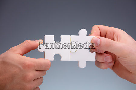two people joining the jigsaw puzzles