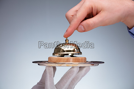 persons hand ringing service bell hold