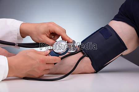 doctor checking male patient arterial blood