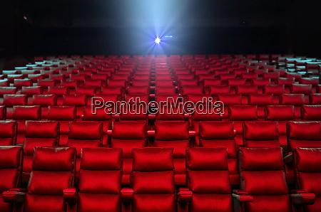 red cinema seats with projector bright