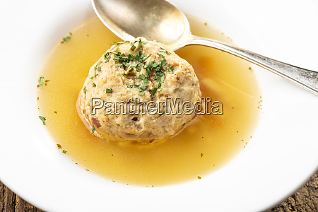 single speckknoedel in soup on wood
