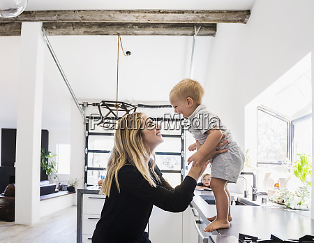 mother holding son on kitchen counter