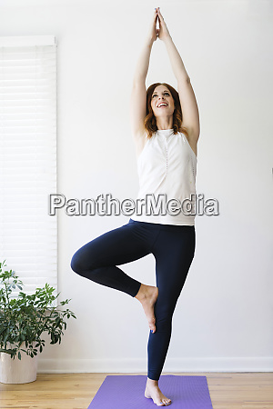 smiling mid adult woman practicing yoga