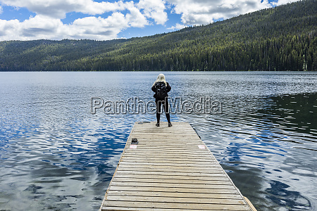 woman standing on jetty on lake