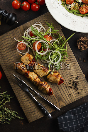 grilled meat skewers and salad on