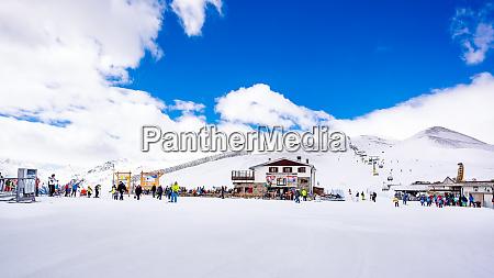 skiers snowboarders relaxing near mountain hut