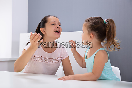 speech therapist helps the girl how