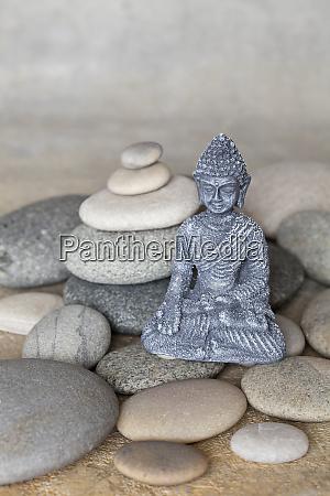 buddha statue and balanced stone cairn