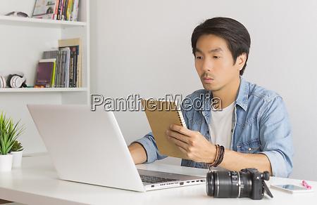 asian photographer or freelancer checking work