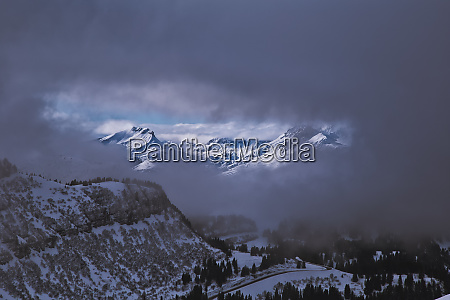 vista between clouds on sunlit mountains