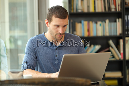 serious man using a laptop in