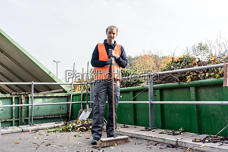 man sweeping the floor of recycling