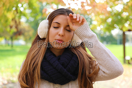 girl with earmuffs suffering migraine headache