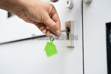 woman using key to open door