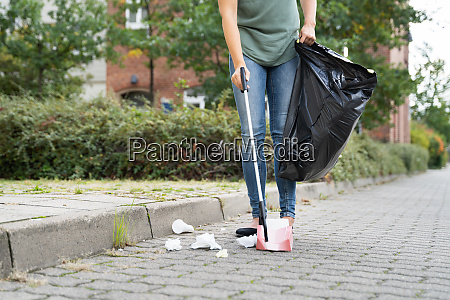 woman collecting trash outdoors
