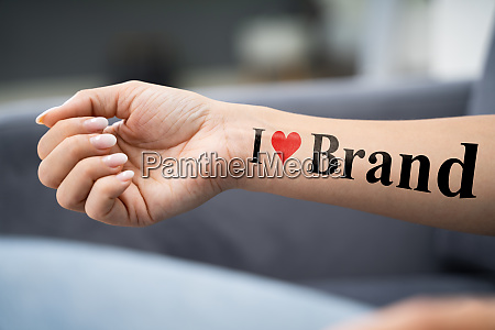 woman showing i love brand tattoo