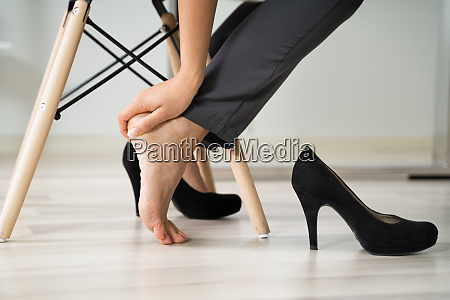 businesswoman rubbing her feet